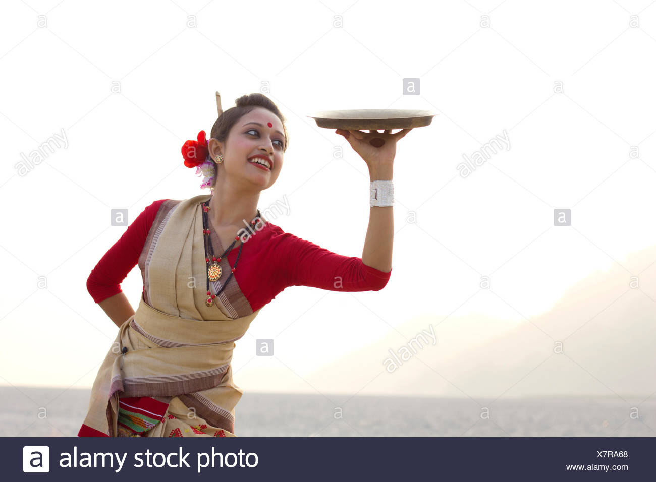 Bihu woman dancing with a brass plate - Stock Image
