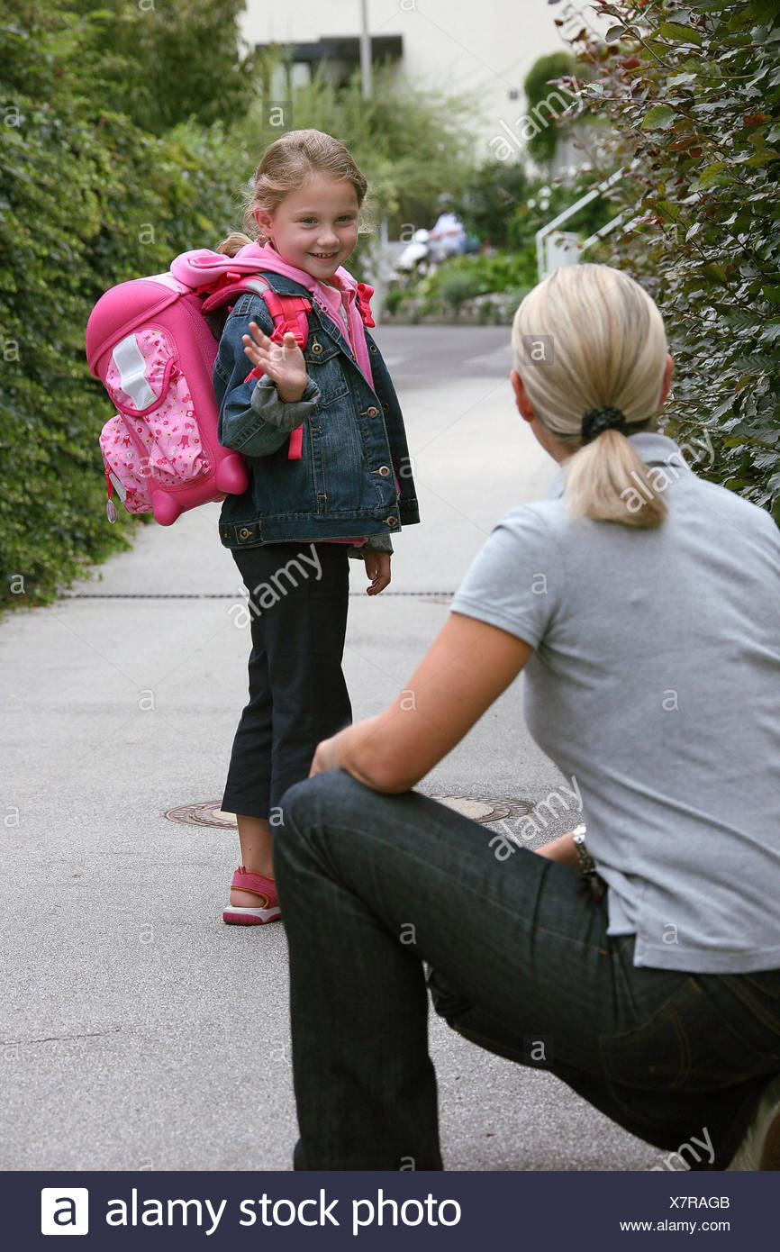 First-grader with a miscounsel satchel and a school-cornet is waving at the mother - Stock Image