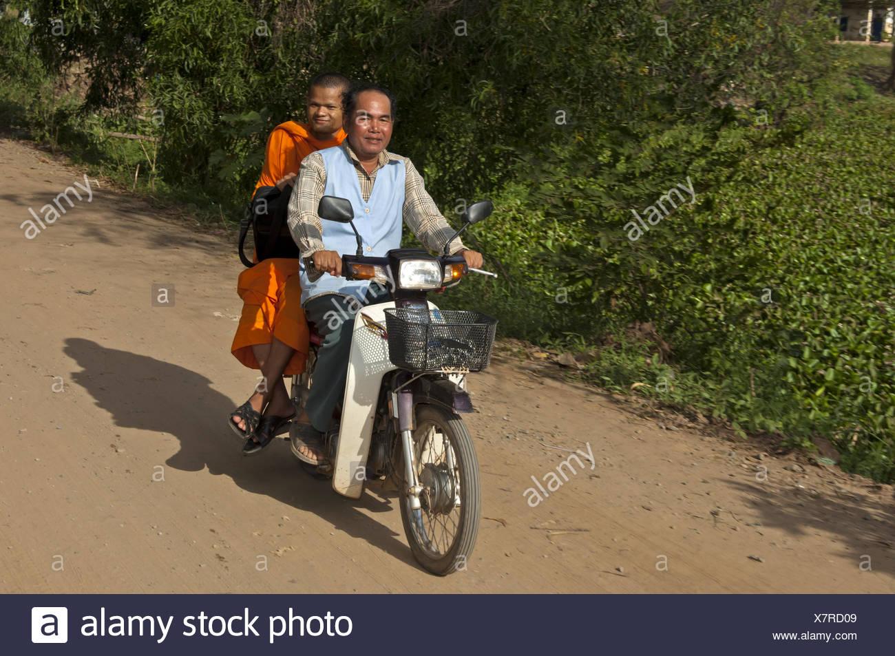 Buddhist monk riding as passenger on a motor-bike Stock Photo