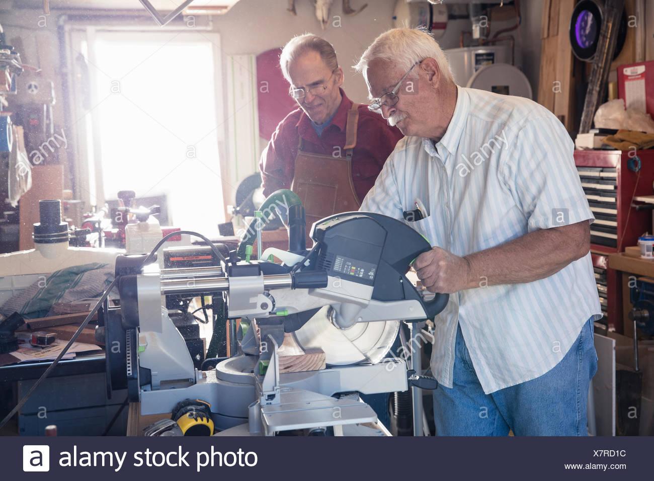 Senior men sawing woodblock in carpentry workshop - Stock Image