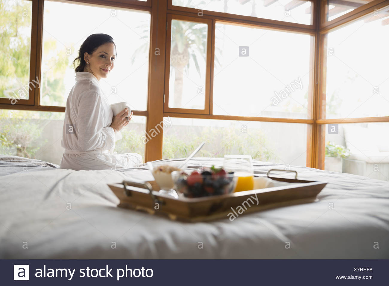 Woman sitting on bed holding coffee cup - Stock Image