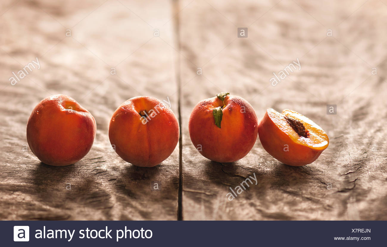 3 whole peaches and one split peach on rustic wood background. Bright, warm setting. - Stock Image