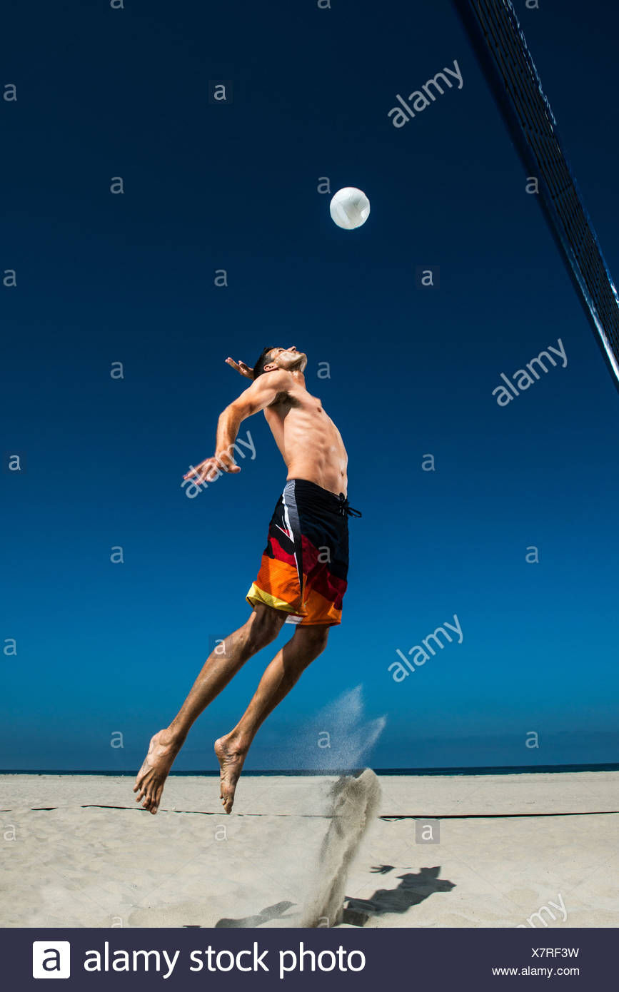 Male beach volleyball player jumping mid air to hit ball - Stock Image