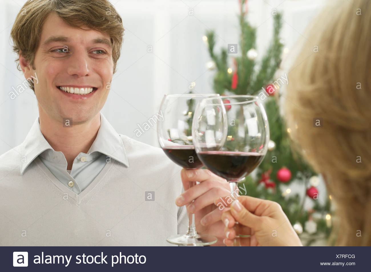 Two people chinking red wine glasses - Stock Image