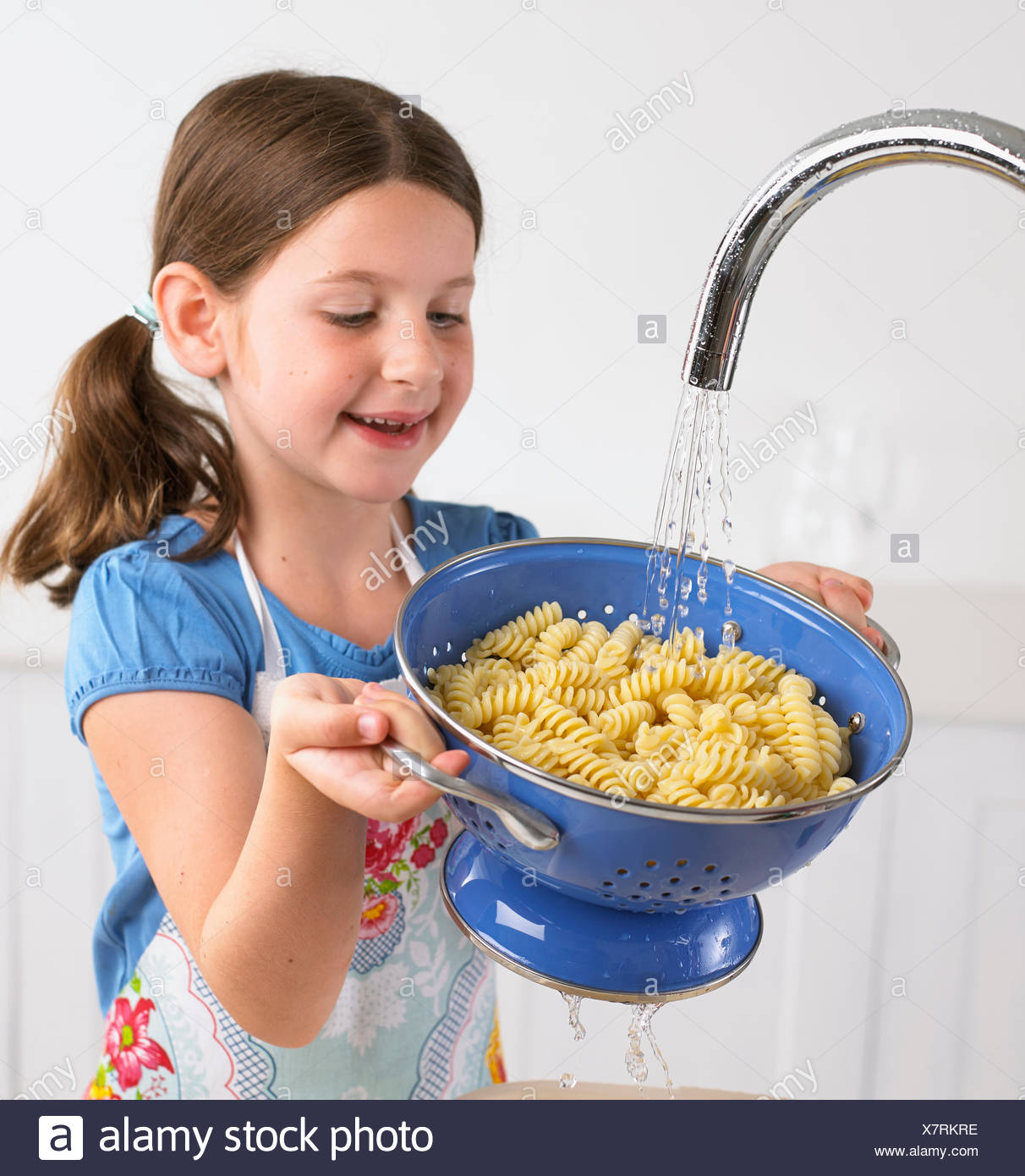 Young girl draining pasta - Stock Image