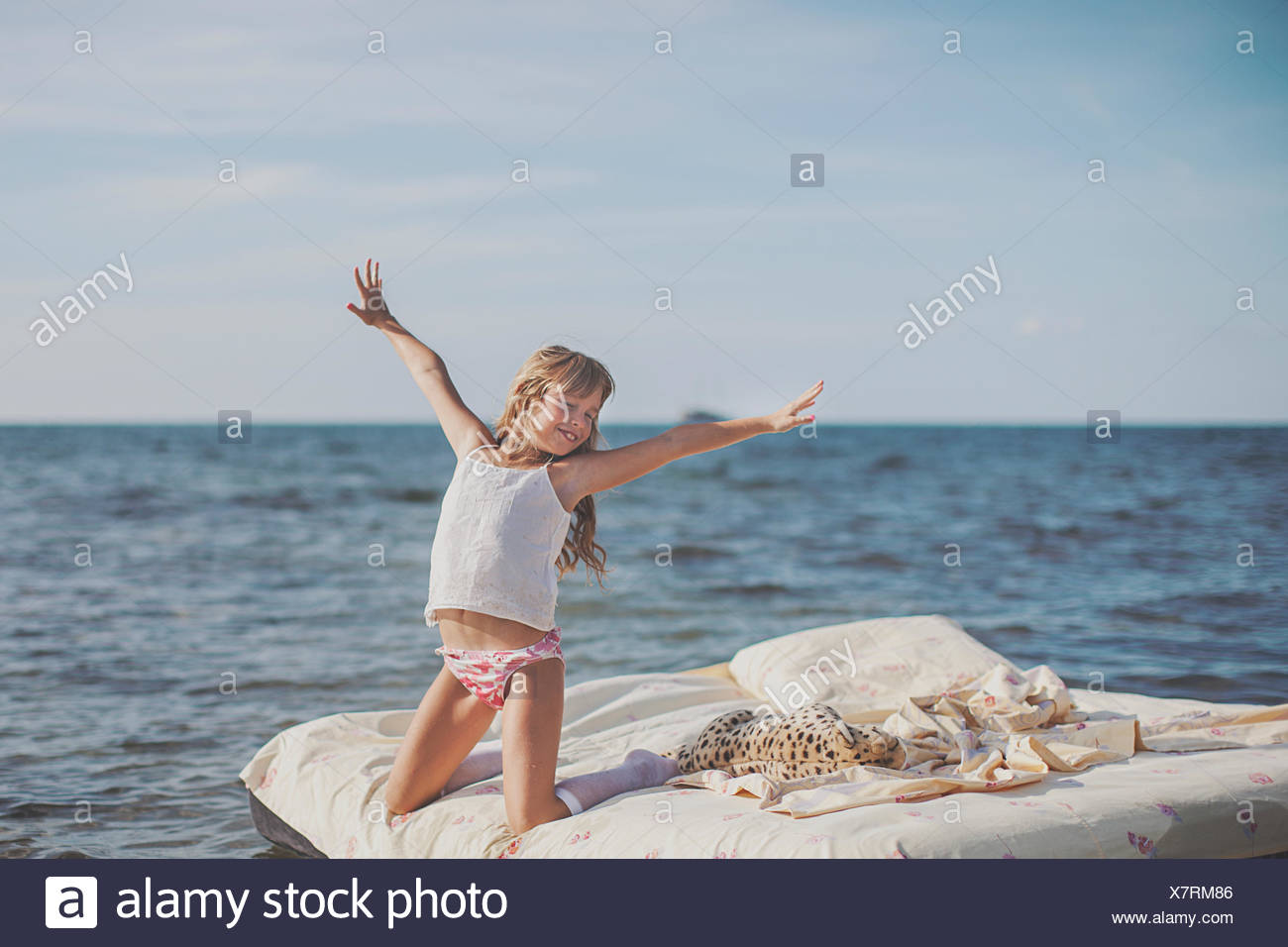 Young blonde haired child (8-9) on air bed at sea - Stock Image
