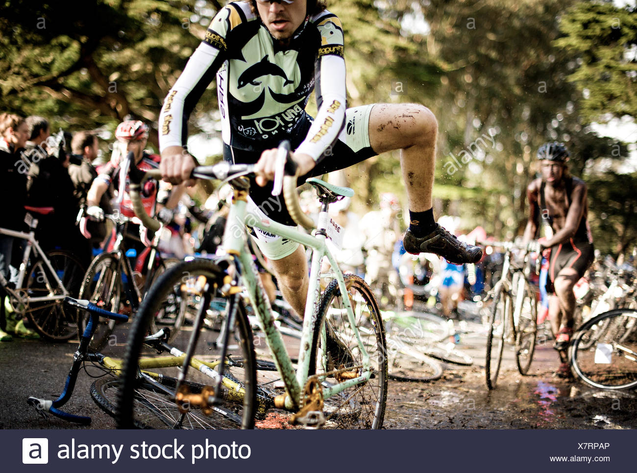 Cyclocross racer grabs bike at race start - Stock Image