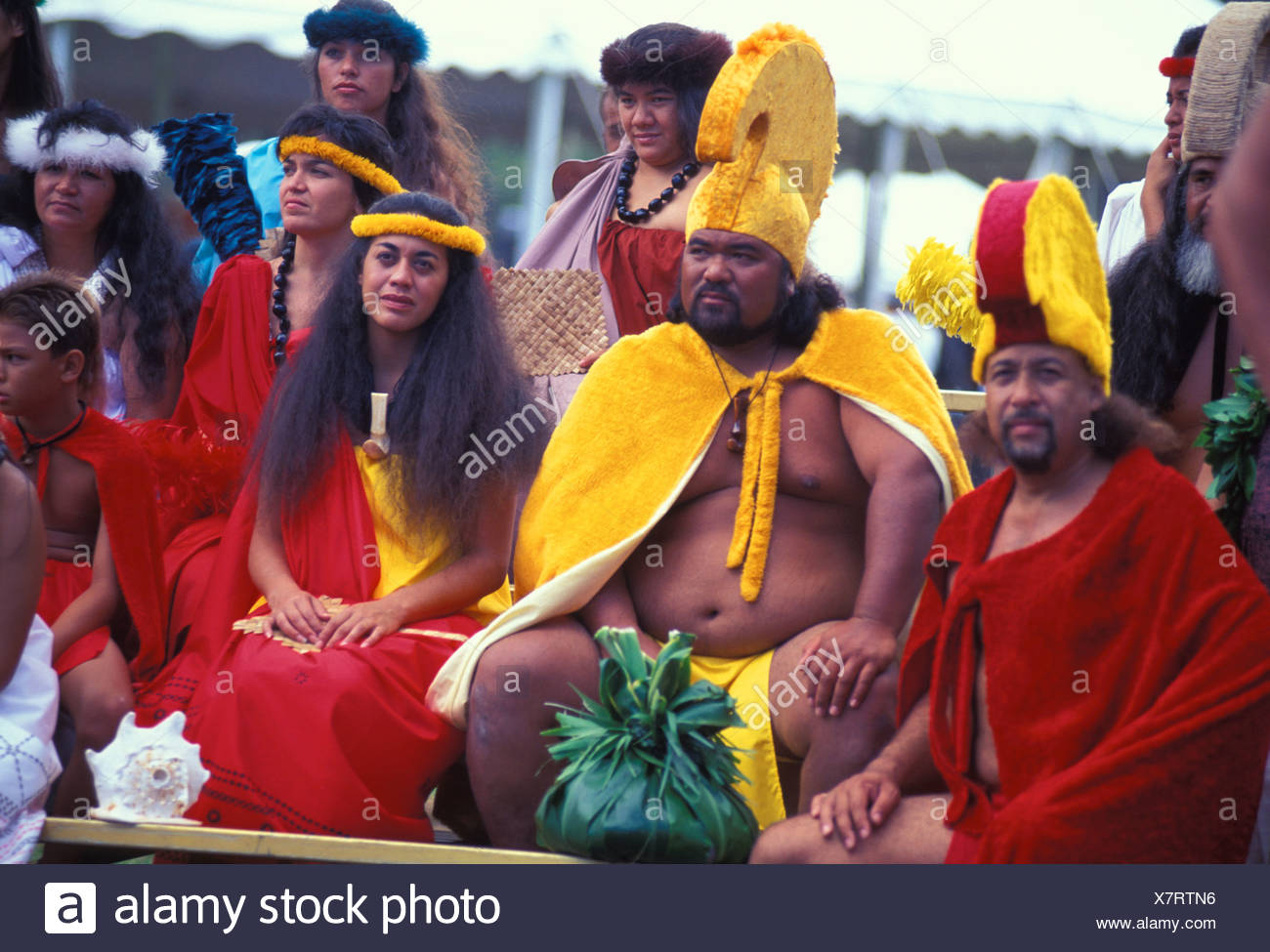 Aloha week festivities with the royal king and queen wearing capes with a puolo ti leaf offering - Stock Image