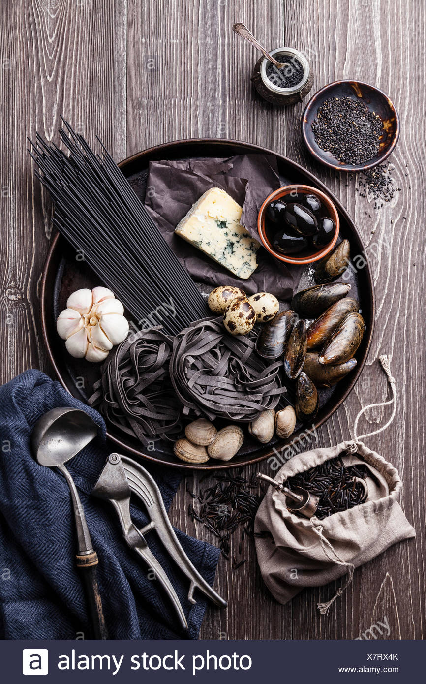 Black raw food ingredients - Pasta, olives, clams on wooden background - Stock Image