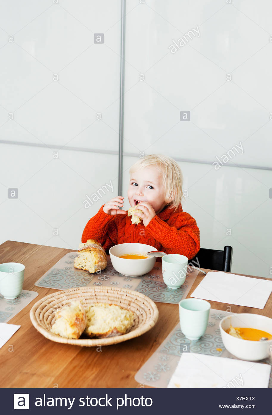 Boy eating lunch at table - Stock Image
