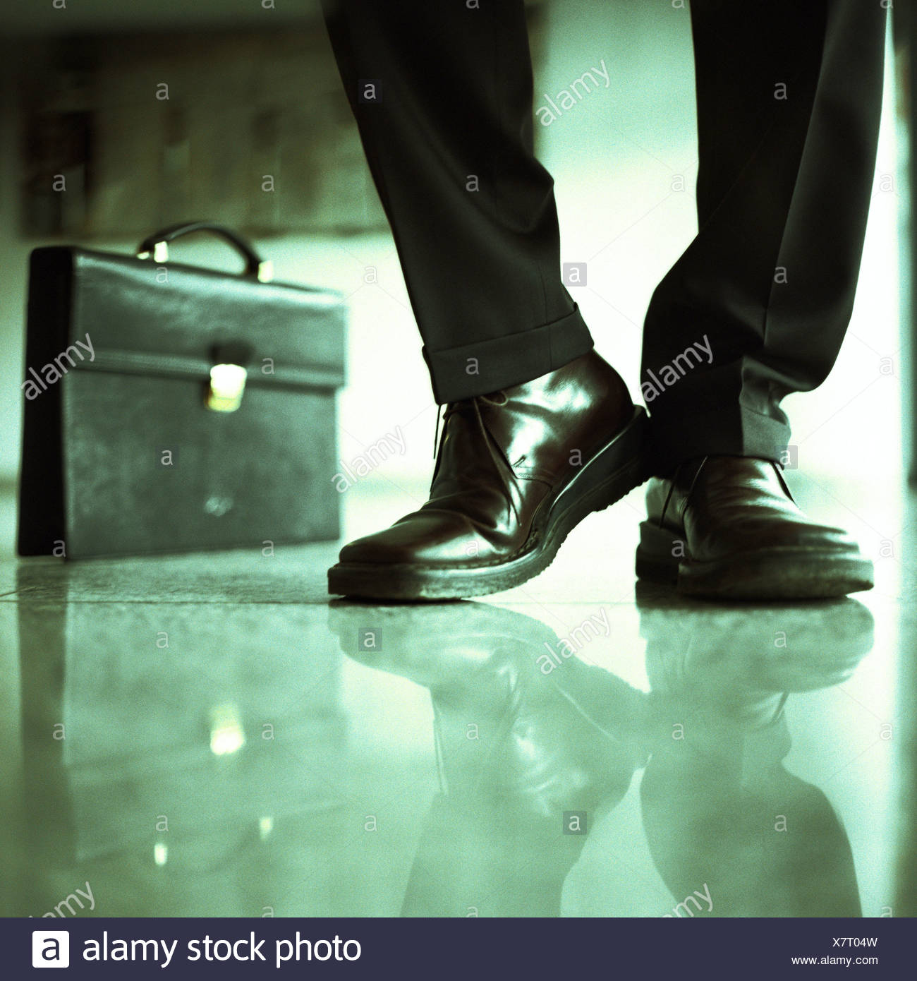 Businessman's lower legs and briefcase - Stock Image