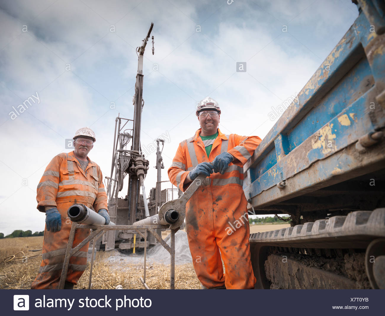 Portrait of drilling rig workers in hard hats and workwear - Stock Image