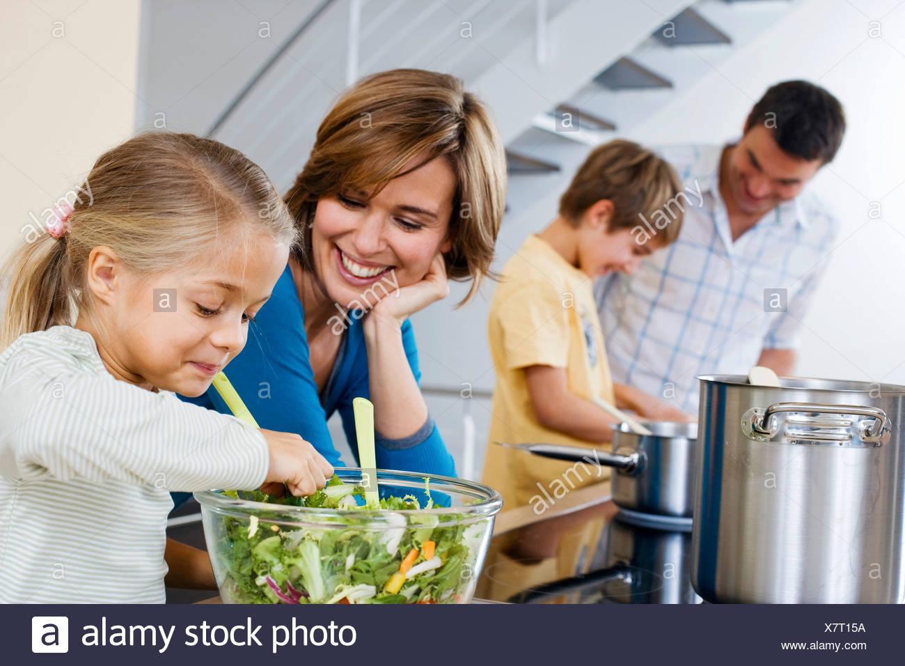 parents cooking with their children in kitchen Stock Photo