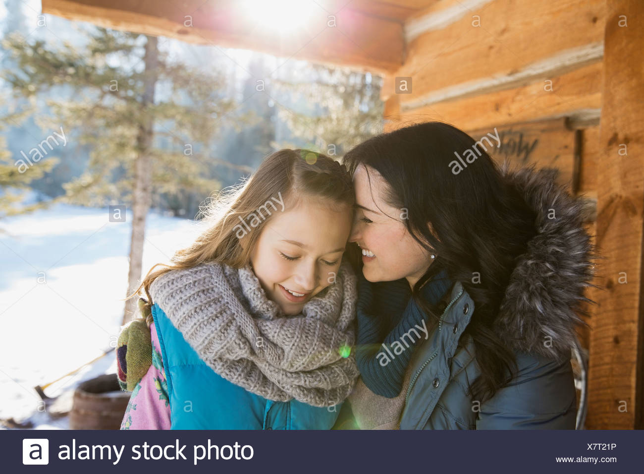 Affectionate mother and daughter outside log cabin - Stock Image