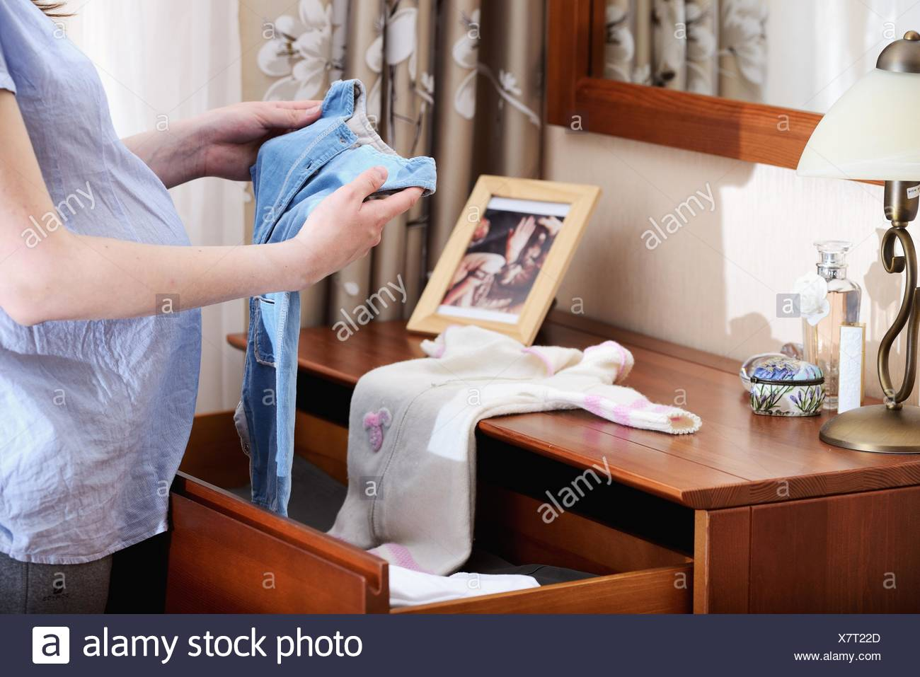 Pregnant woman holding baby clothes, mid section - Stock Image