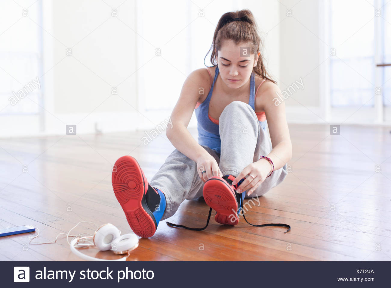Teenage girl tying trainer laces in ballet school - Stock Image