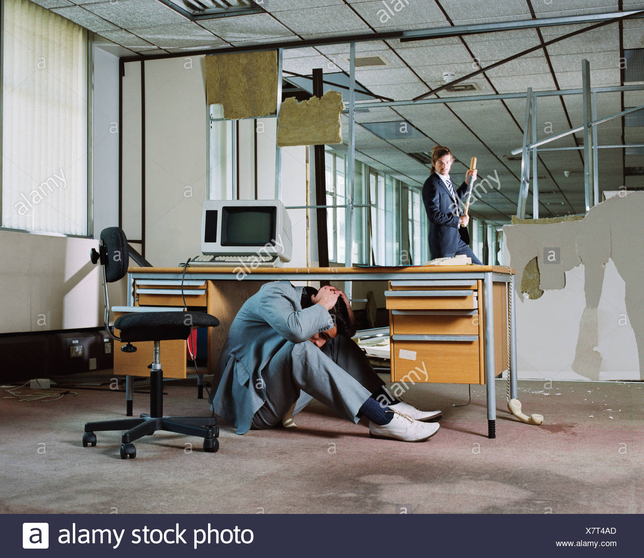 Businessman hiding from colleagues attack - Stock Image