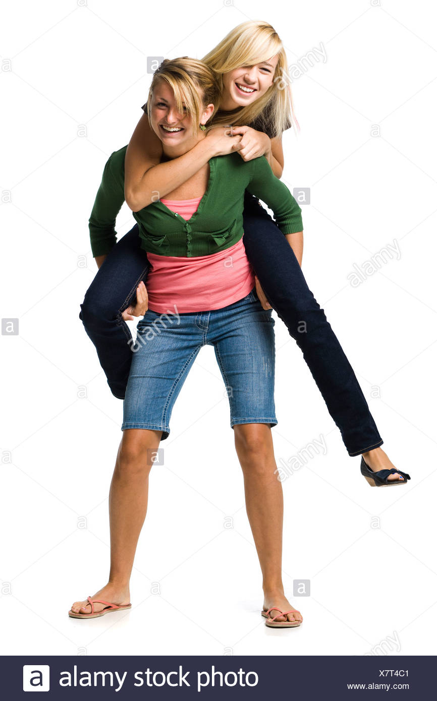 Two teenage girls laughing and giving piggy back ride - Stock Image