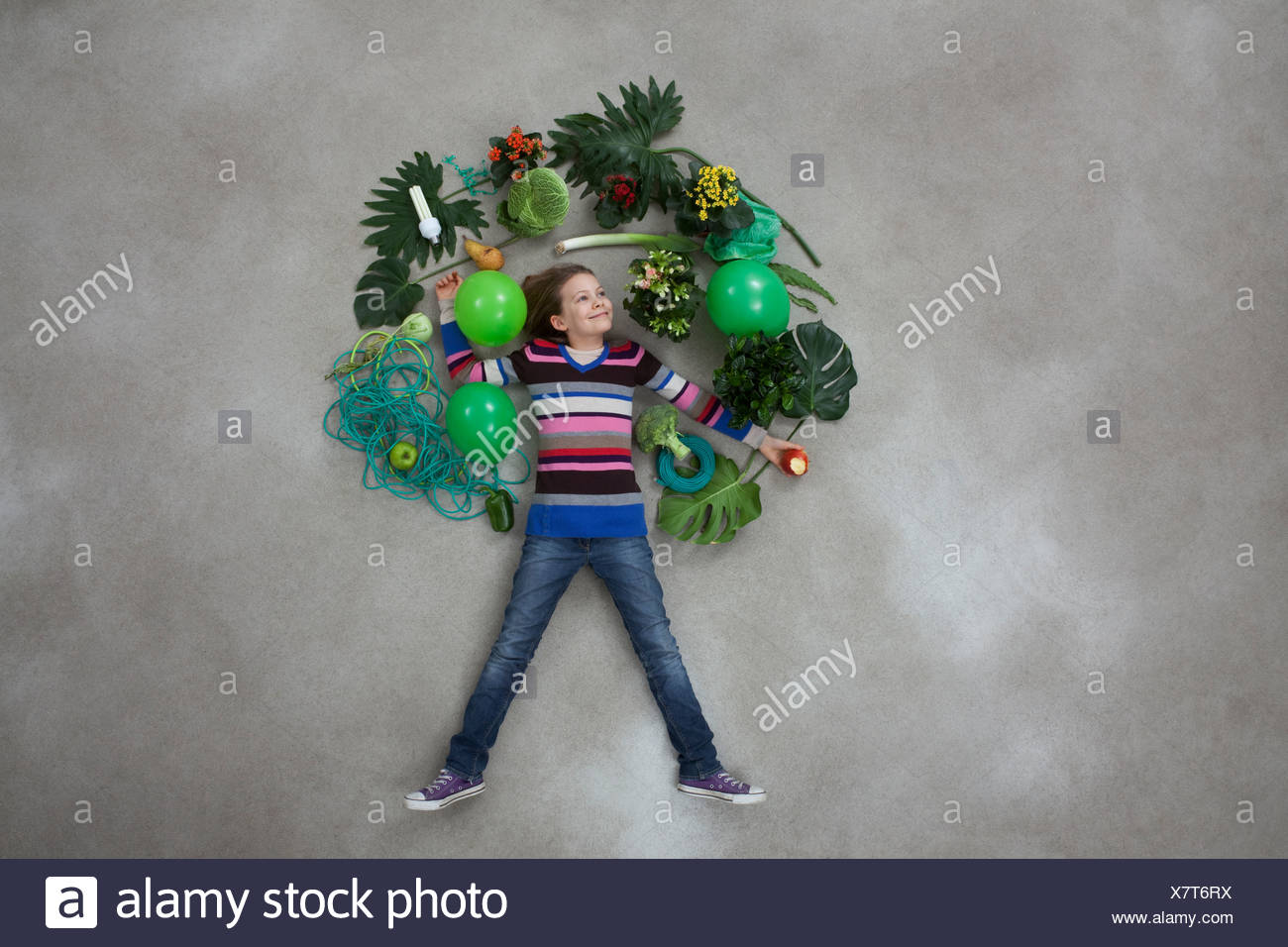 Girl forming tree shape on gray background - Stock Image