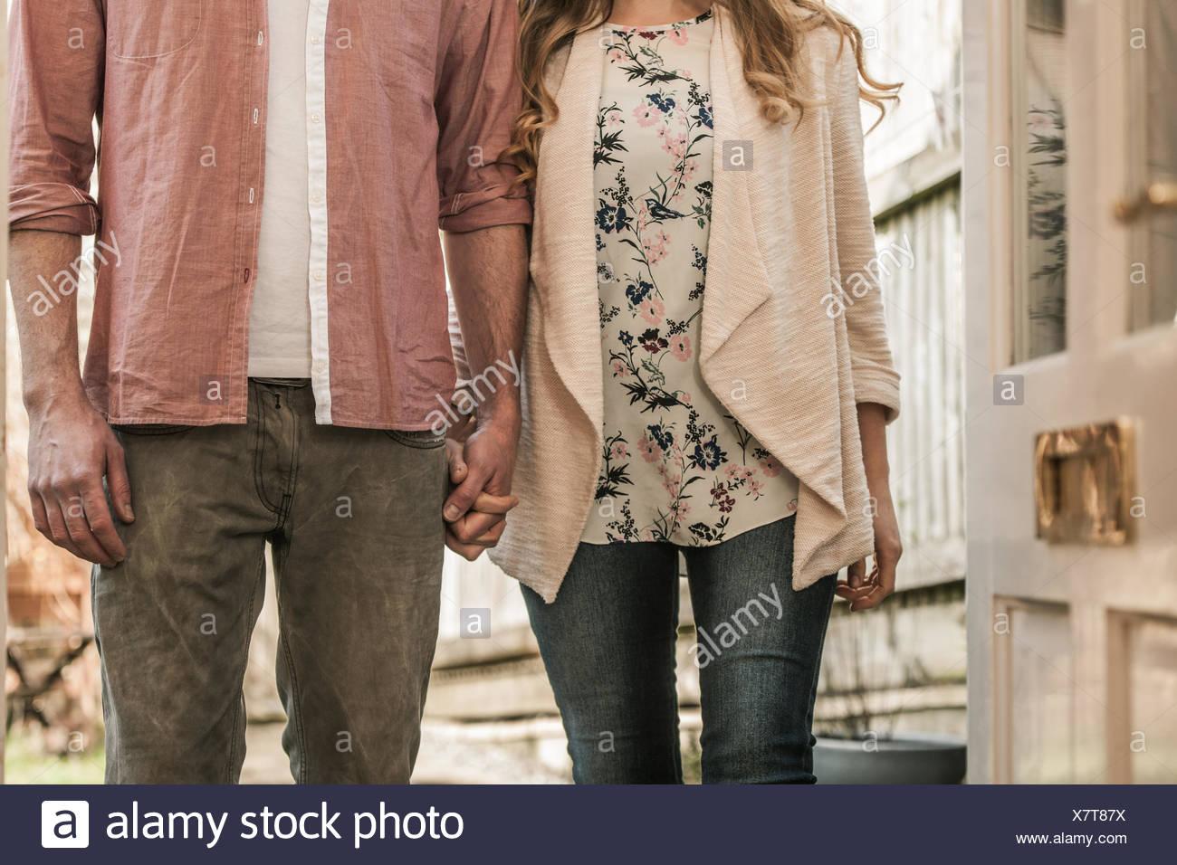 Couple standing outside an open door - Stock Image