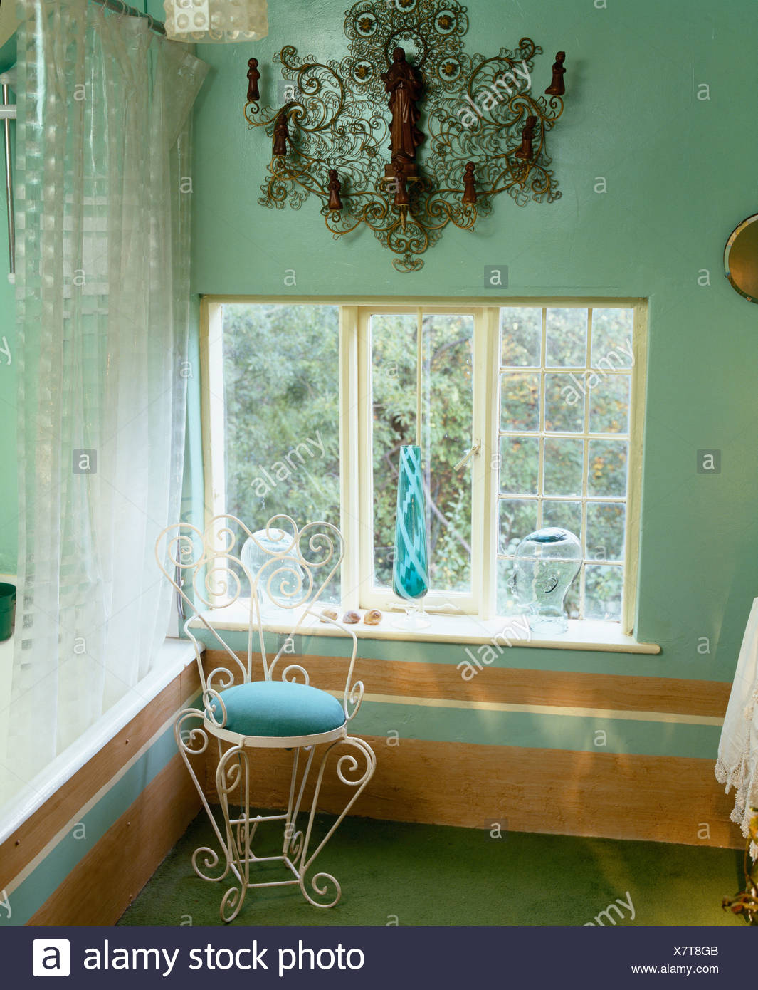 Ornate metal wall sconce above window of pale green bathroom with ...