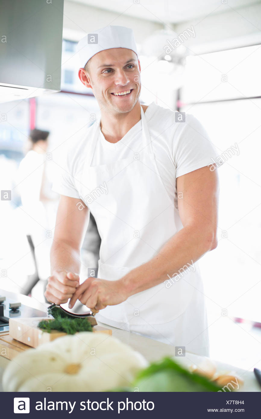 Male chef mixing chopping herbs in commercial kitchen - Stock Image