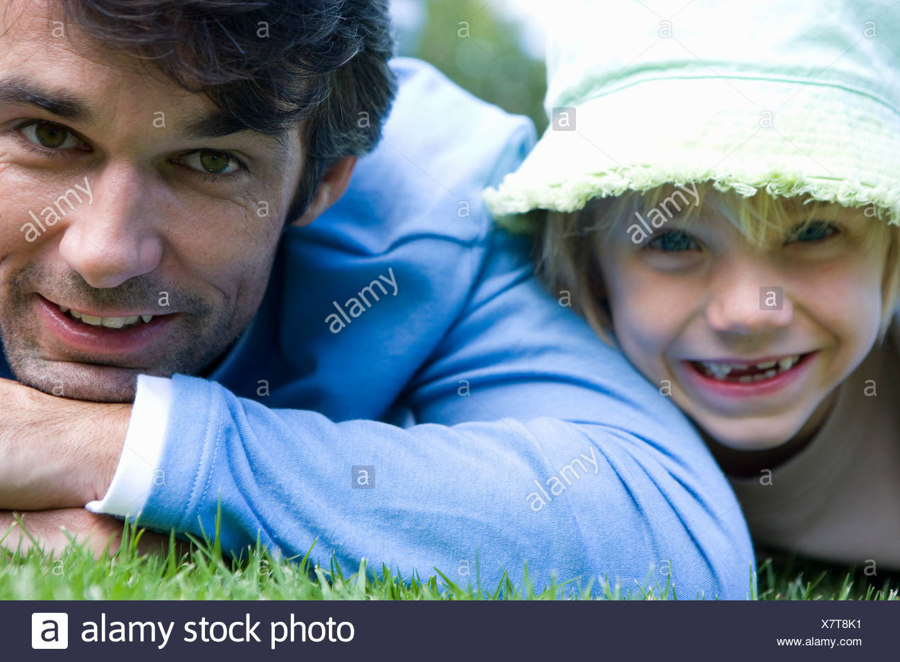 Father and daughter  lying on stomachs on grass, smiling, portrait, close-up - Stock Image