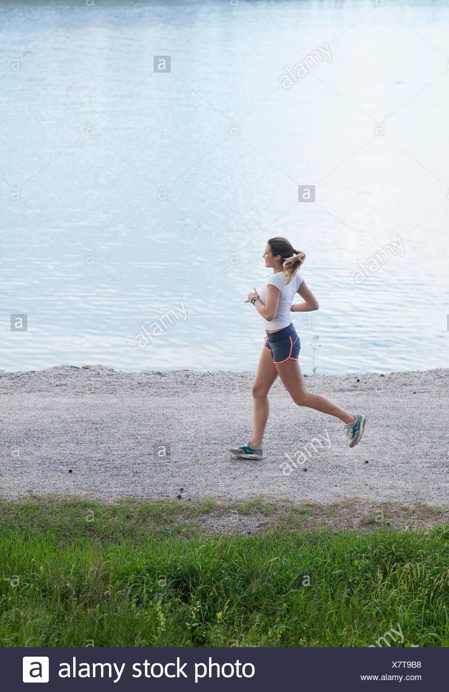 Finland, Uusimaa, Espoo, Teenage girl (16-17) jogging along lakeshore - Stock Image