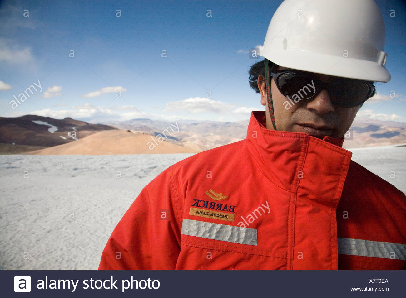 An employee of Barrick Gold stands on the glacier at the