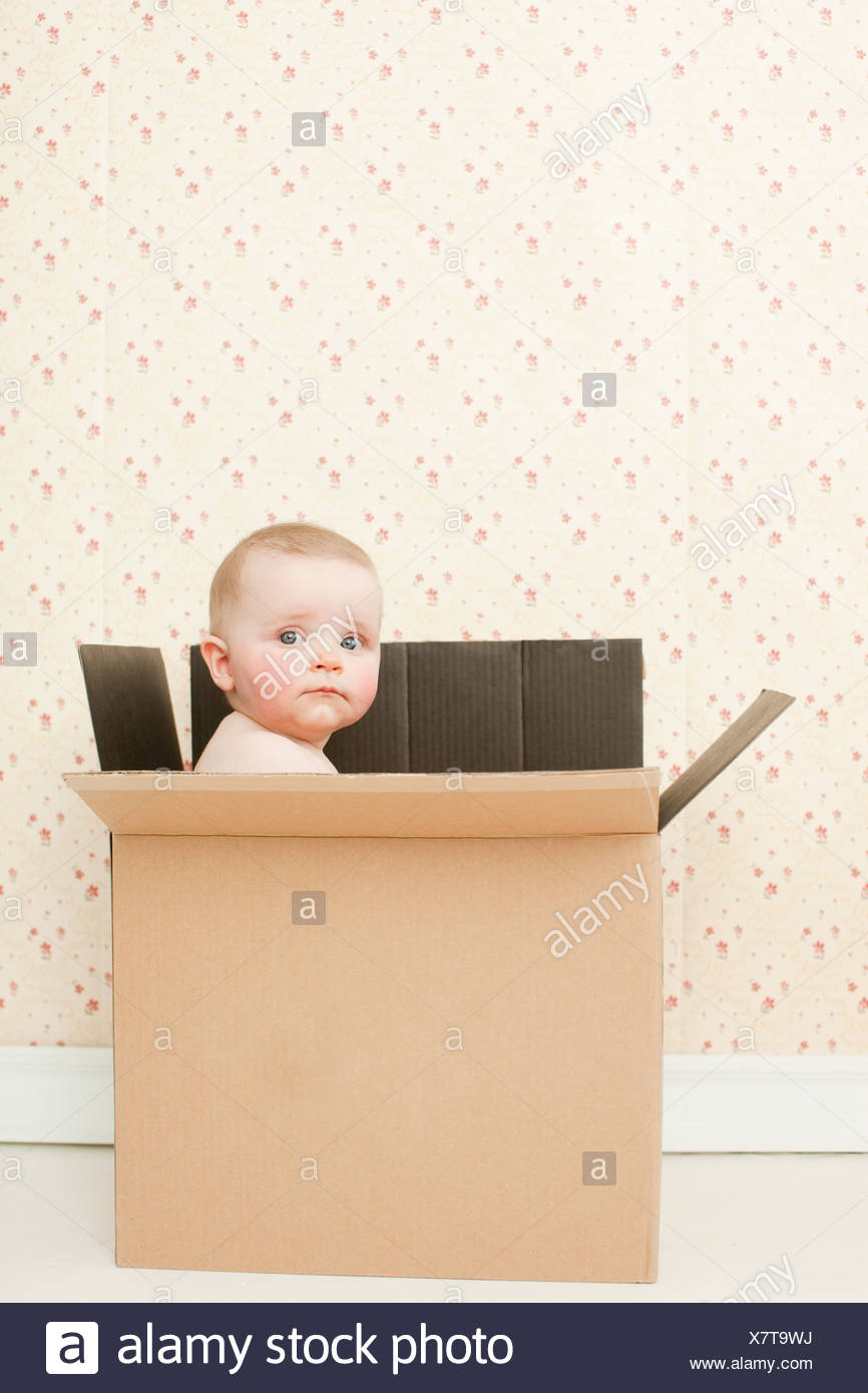 Baby girl in a cardboard box - Stock Image