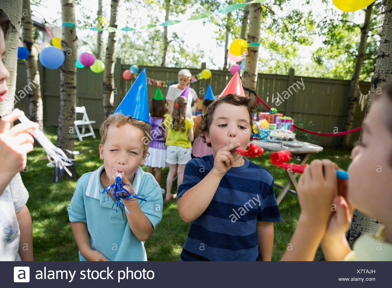 Kids in birthday party hats blowing party favors - Stock Image