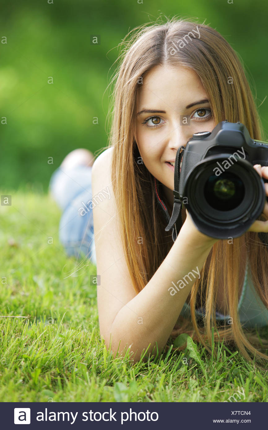 Portrait of beautiful smiling blonde girl , making photos at summer green park. - Stock Image