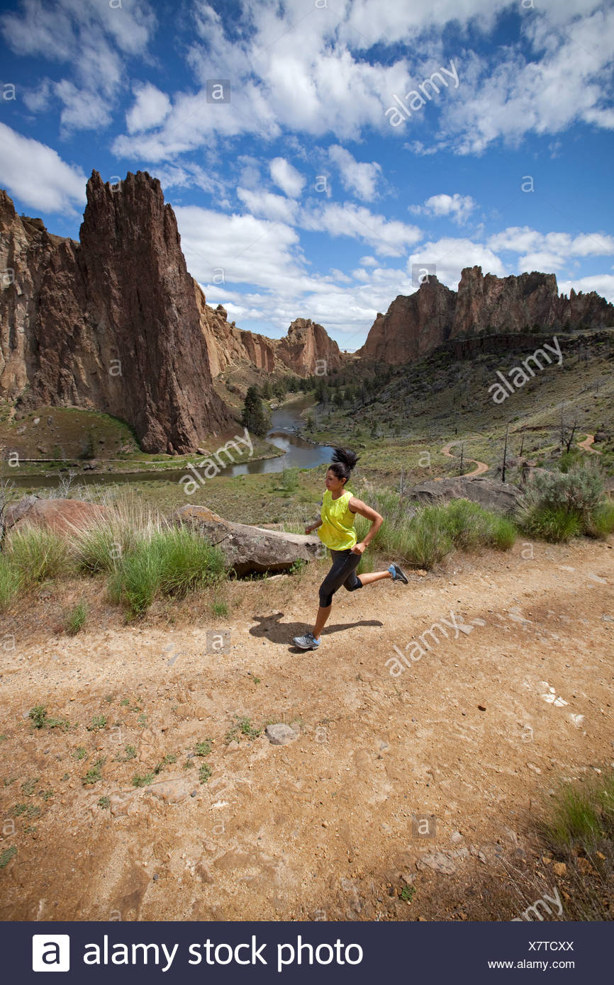 Female trail running with river in distance. - Stock Image