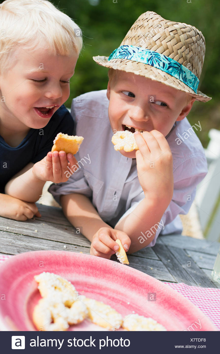 Two boys (4-5, 6-7) eating cookies - Stock Image