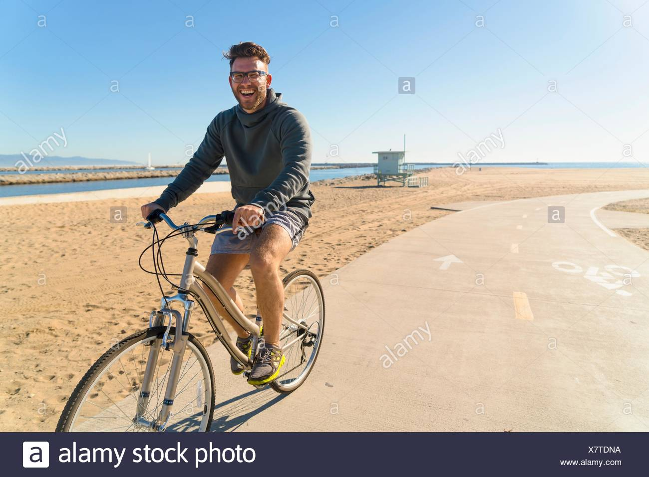 Young man cycling along pathway at beach - Stock Image