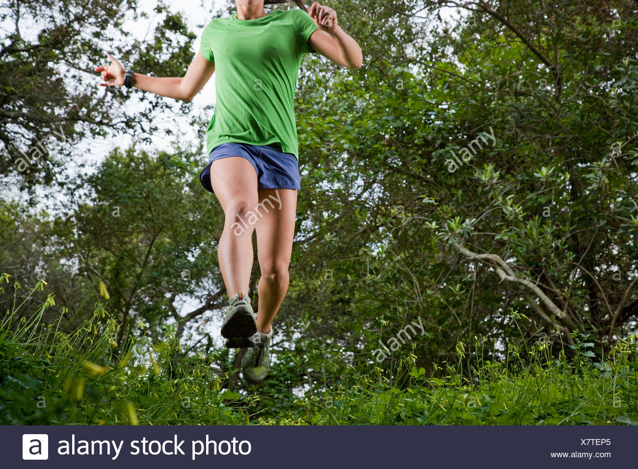 View from below of a woman trail running through a green meadow in the woods. - Stock Image