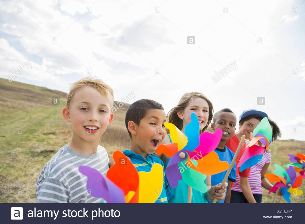 Portrait of schoolchildren holding pinwheels outdoors - Stock Image