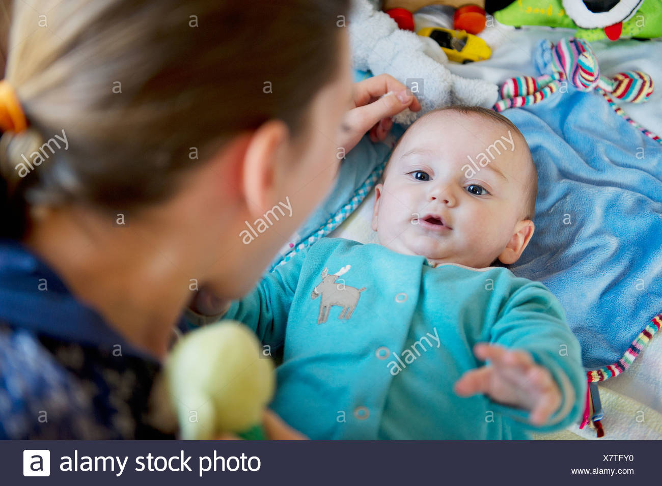 Girl playing with baby brother on bed - Stock Image