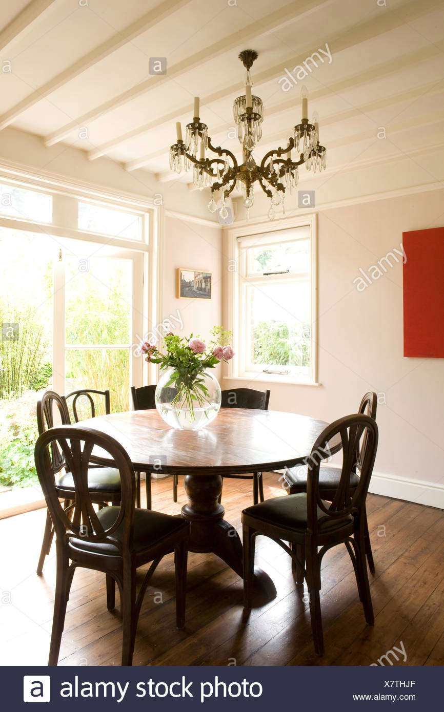 Chandelier above antique table and chairs in modern country dining room Stock Photo