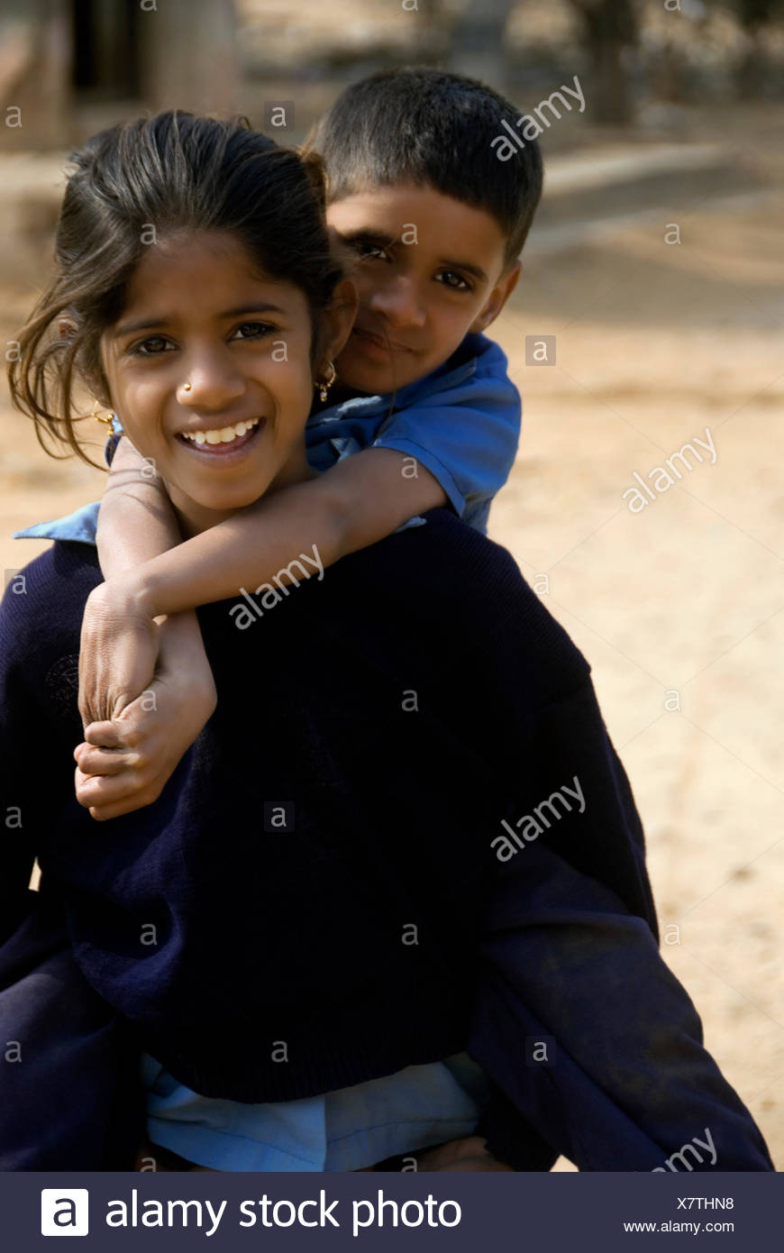 Girl carrying her younger brother - Stock Image