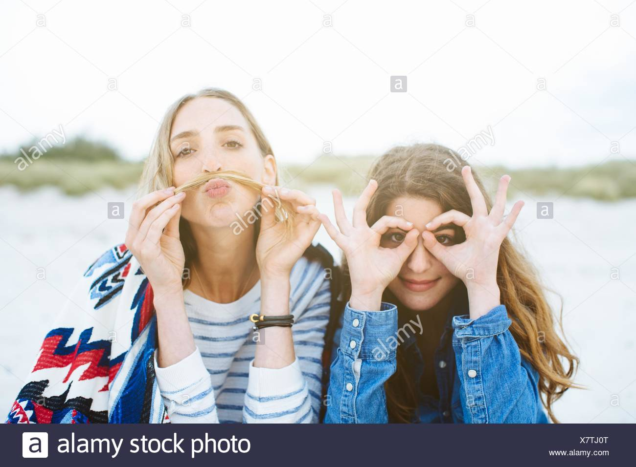 Portrait of two young female friends making moustache and spectacled faces on beach Stock Photo
