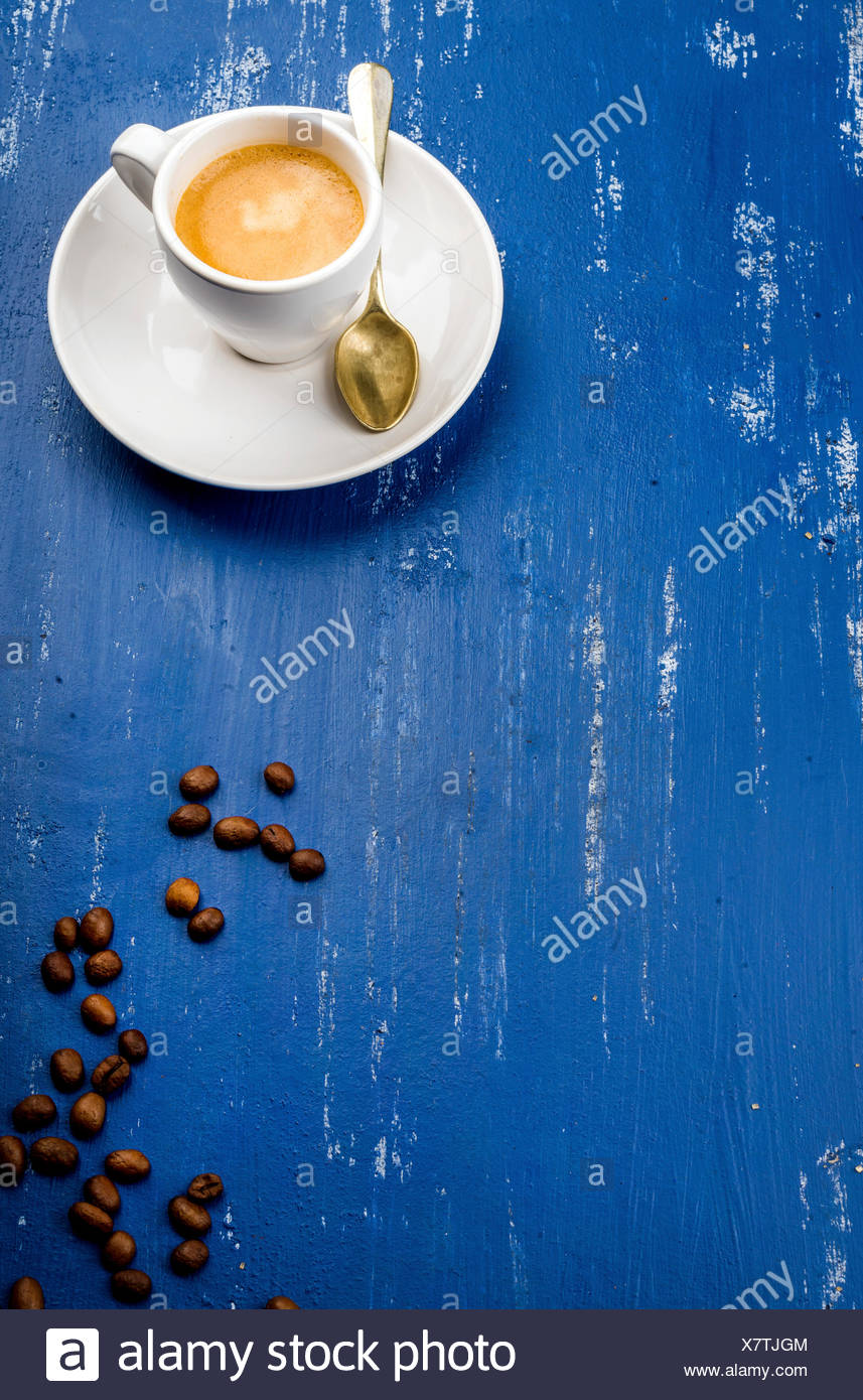 Cup of espresso coffee and beans on wooden blue painted table background. Top view, vertical - Stock Image