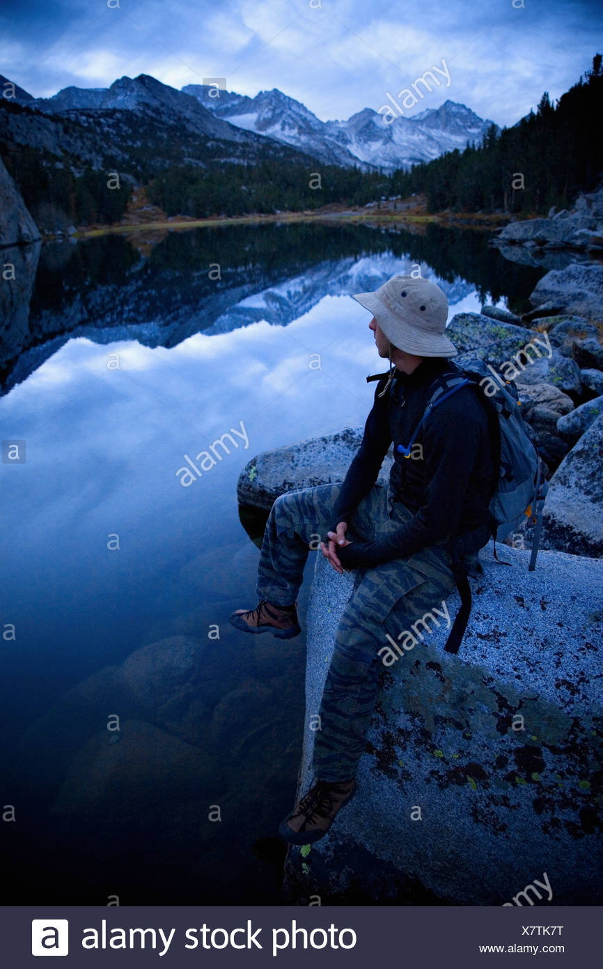 Hiker resting by a lake. - Stock Image