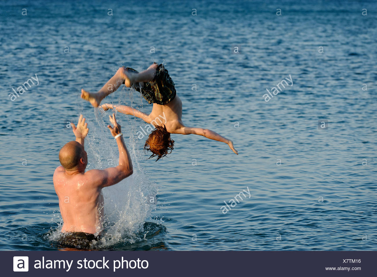 Father and son splashing around in the sea - Stock Image