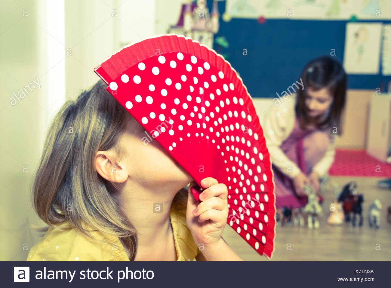Little girl playing with fan - Stock Image
