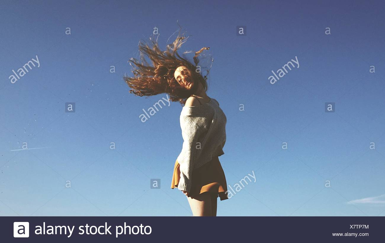 Young Woman Tossing Hair Against Clear Blue Sky - Stock Image