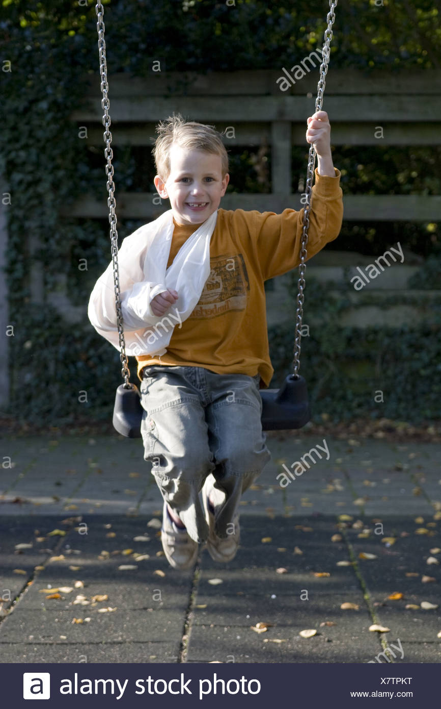 Boy daredevil playing with fractured-arm at playground - Stock Image