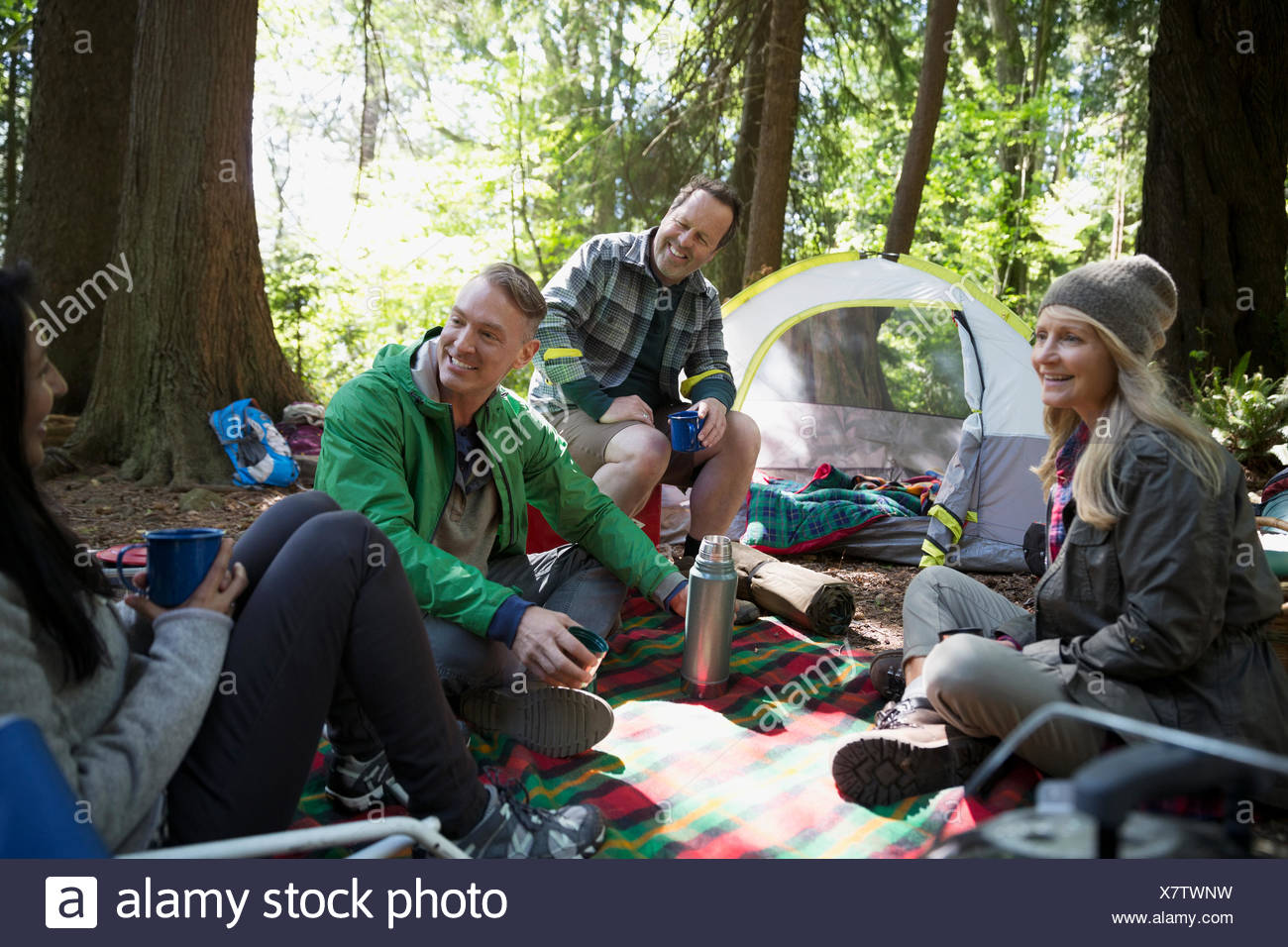 Friends talking and relaxing at campsite - Stock Image