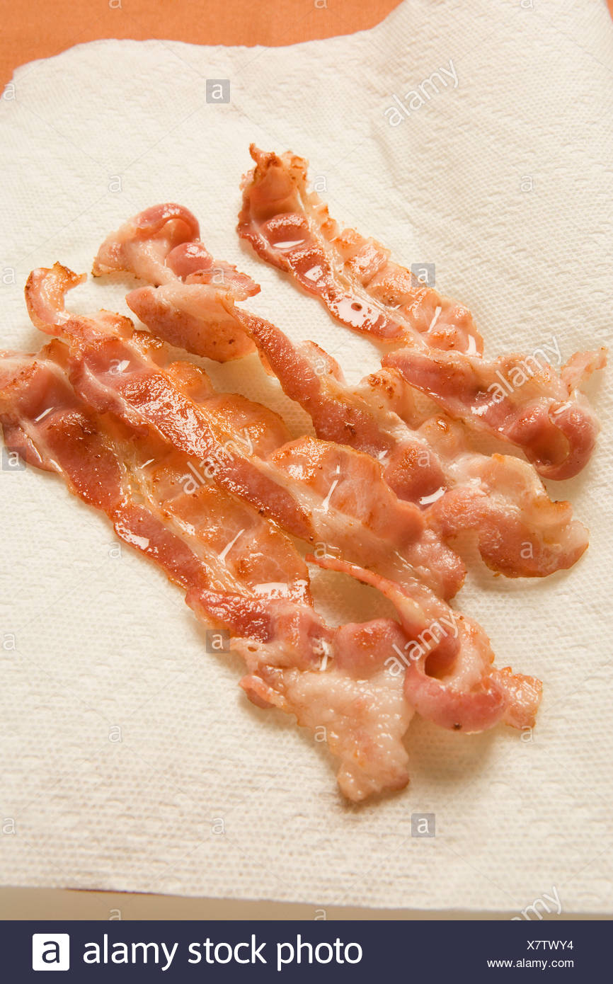 Slices of fried bacon on absorbent kitchen paper 2 FoodCollection Stock Photo