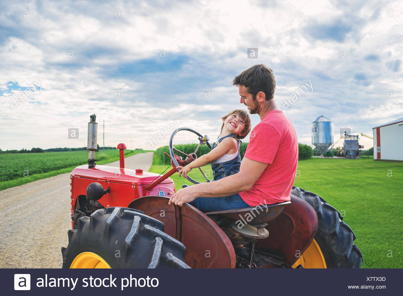 Father driving a tractor with his son - Stock Image